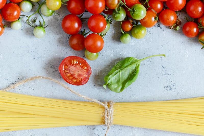 Jedzenie rama Makaronów składników pojęcie Uncooked spaghetti i czereśniowy pomidor z zielonym basilem na błękitnym tle Odgórny w obrazy royalty free