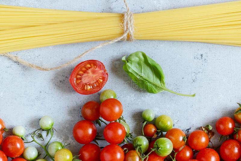 Jedzenie rama Makaronów składników pojęcie Uncooked spaghetti i czereśniowy pomidor z zielonym basilem na błękitnym tle Odgórny w obraz stock