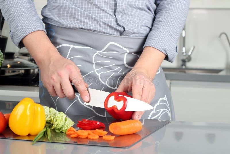 Jedzenie, rodzina, kucharstwo i ludzie pojęć, - Obsługuje ciapanie paprykę na tnącej desce z nożem w kuchni zdjęcie stock