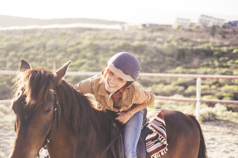 Jedzie z hełmem dla pięknej atrakcyjnej młodej kobiety z ładnym uśmiechem cajgi i przypadkowi ubrania dla plenerowych dziewczyn w fotografia royalty free