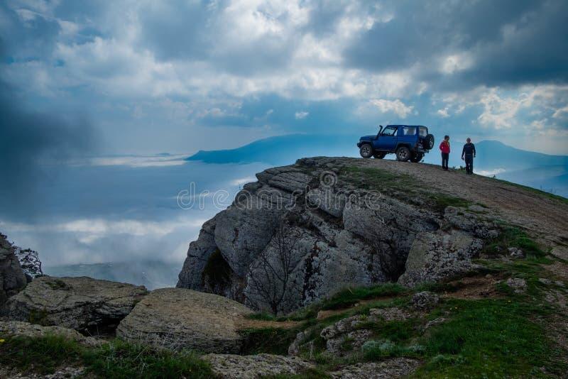 Jeep che sta su una roccia sopra le nuvole immagine stock
