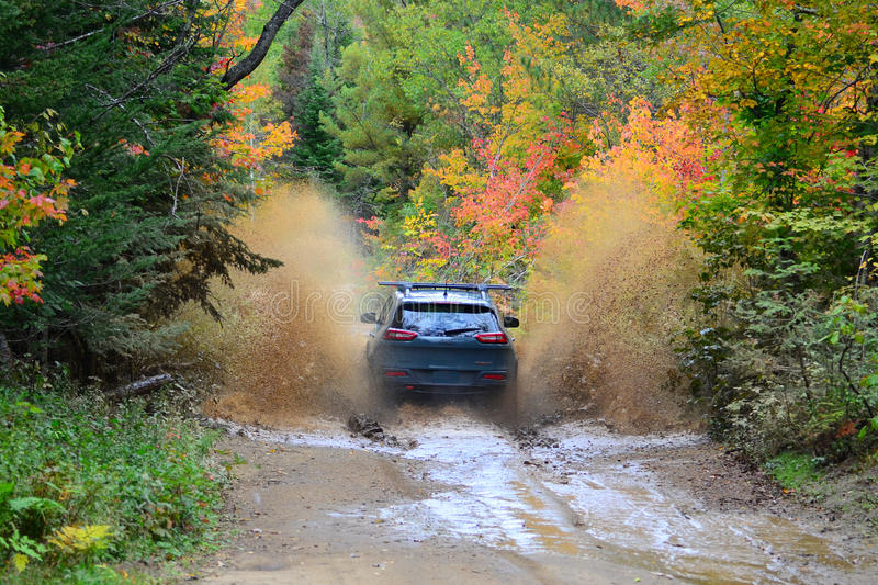 Jeep Cherokee TrailHawk 4x4 going offroad through waterhole. New Jeep Cherokee TrailHawk 4x4 offroad driving through water hole spraying water and mud stock photography