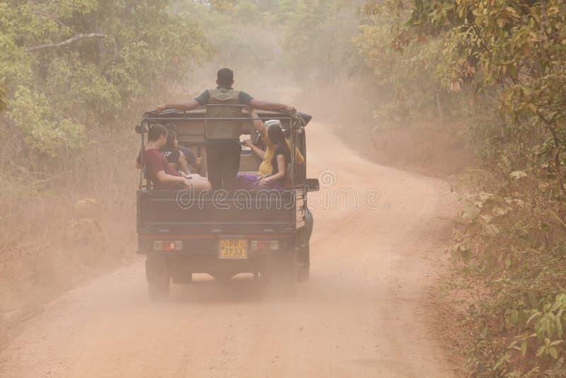 Jeep com turistas na estrada de terra no Parque Natural de Minneriya, no Sri Lanka Nuvem de poeira imagem de stock royalty free