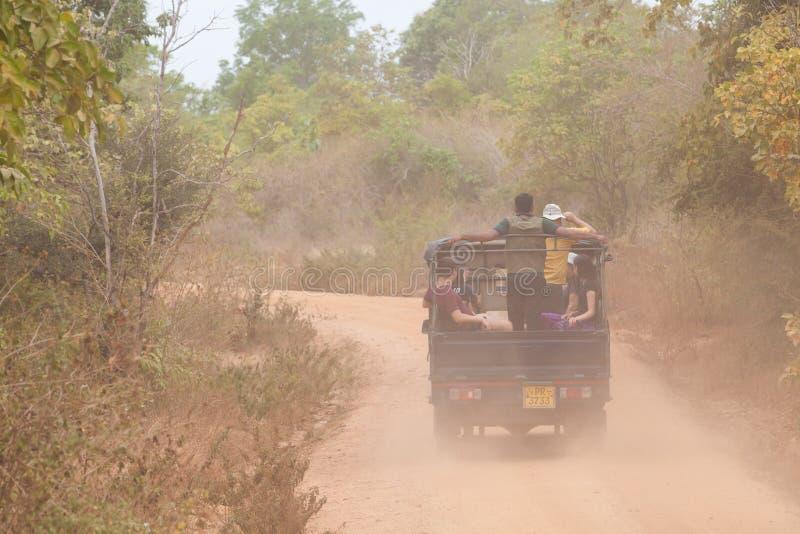 Jeep con turisti sulla strada sterrata nel parco naturale di Minneriya in Sri Lanka Nuvola di polvere immagine stock libera da diritti