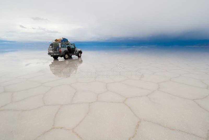 Jeep i den salt laken salar de uyuni, bolivia fotografering för bildbyråer