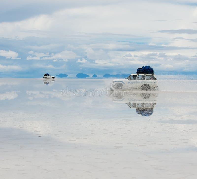 Jeep nel lago di sale salar de uyuni fotografia stock