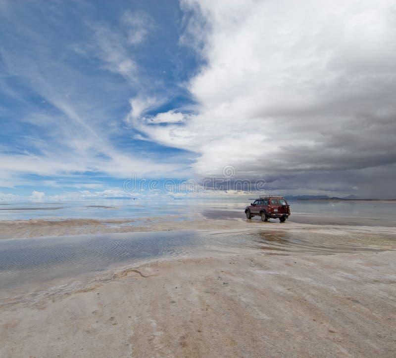 Jeep nel lago di sale salar de uyuni, Bolivia fotografie stock