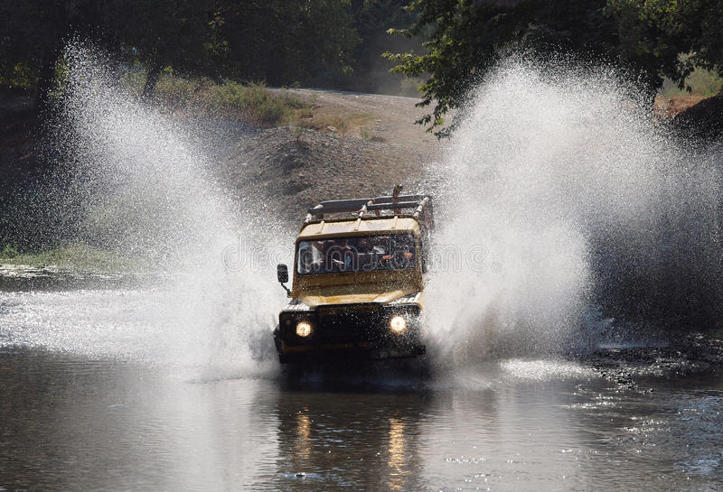 Jeep Safari through River. Motion image of a jeep safari going through a river with splashing water royalty free stock photography