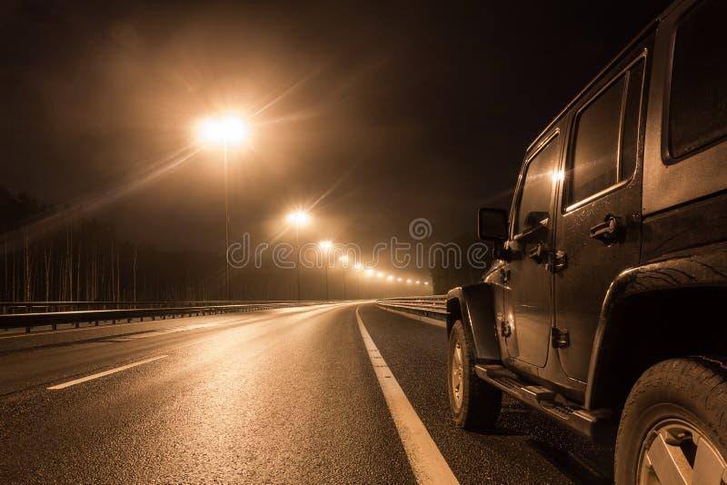 Jeep Wrangler natt på en öde väg i den Leningrad regionen arkivfoton