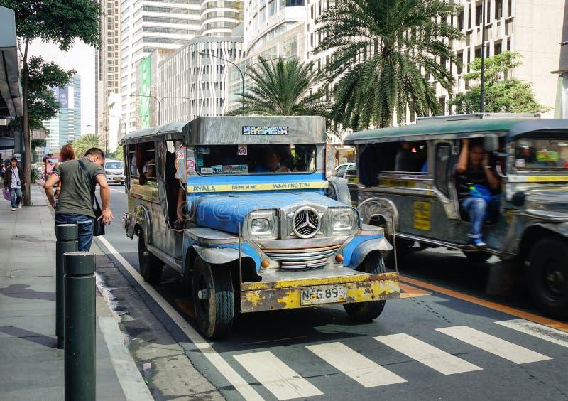 Jeepney corre en el camino de Ayala en Manila, Filipinas fotos de archivo