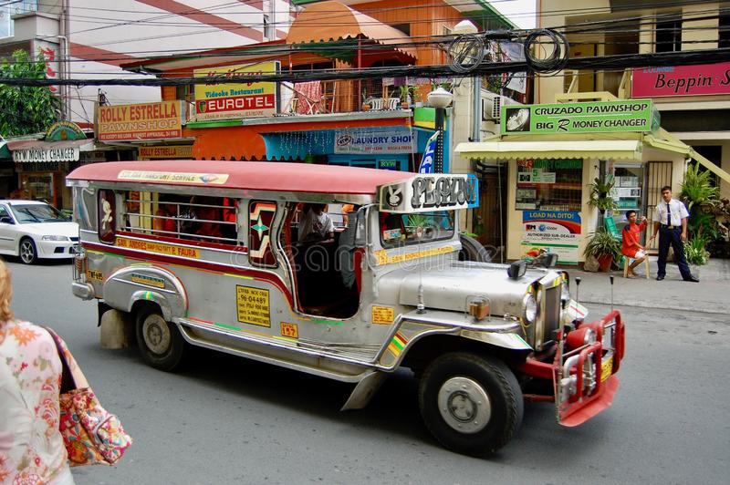 A Jeepney taxi drives down the street/road in downtown Manila with designs and colourful decorations on the vehicle royalty free stock images