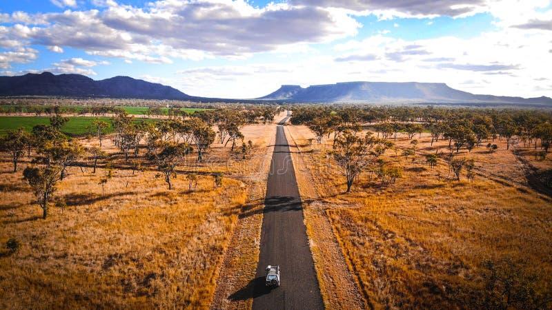 Jeepreise der Autoreise 4wd nach Ayers-Felsen durch die ländlichen Hinterland-Australien-Täler im Wüstenland mit Bergen im backgr stockbild