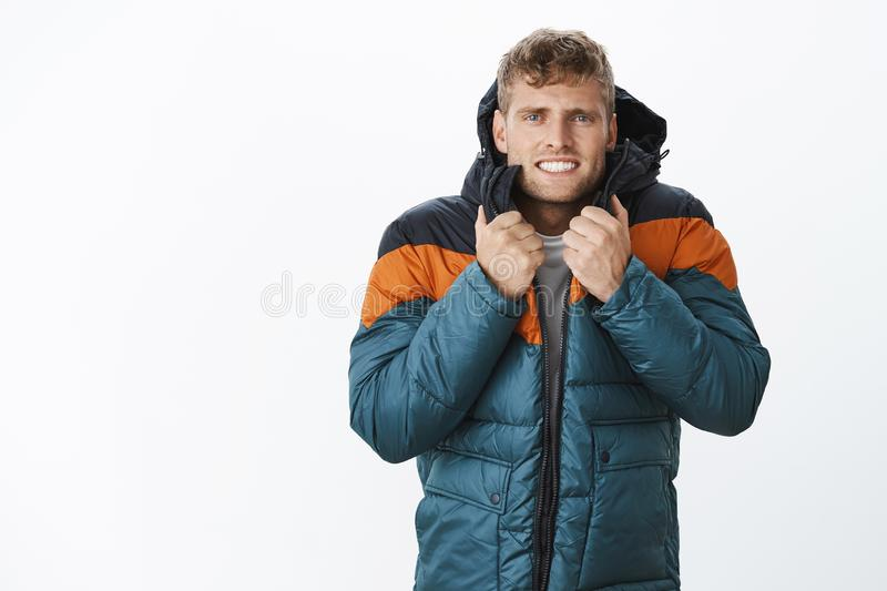 Jeez freezing cold. Portrait of intense trembling handsome european blond man clenching teeth wearing winter puffer royalty free stock photo