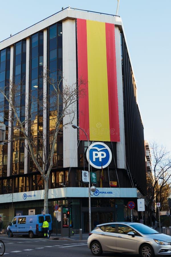 Jefaturas populares de Partido que construyen en Génova 13 Bandera española grande en la fachada y el logotipo de los PP foto de archivo