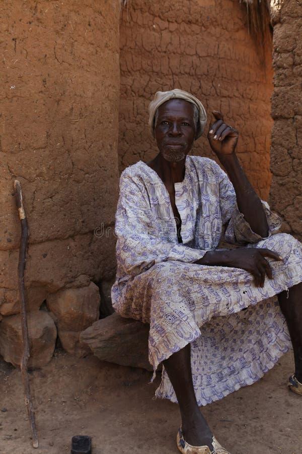 Jefe africano del pueblo que descansa en la sombra de su choza foto de archivo libre de regalías
