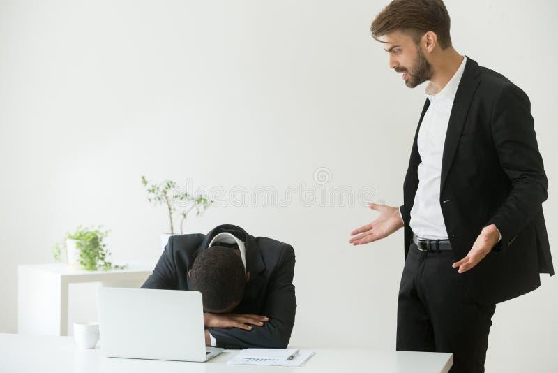 Jefe caucásico malo enojado que grita regañando al africano frustrado a imagen de archivo