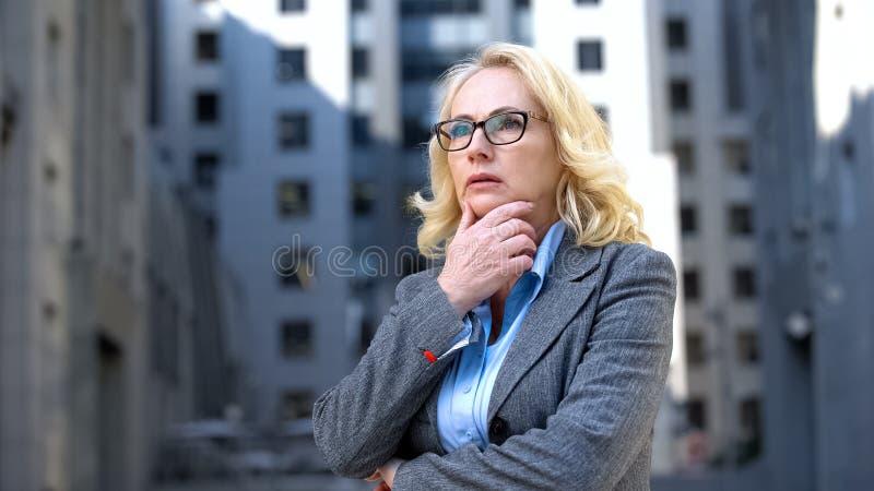 Jefe de dama ansioso con la mano en la toma de decisiones, problema de trabajo, elección de carrera imagen de archivo
