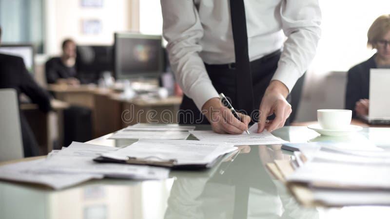 Jefe de los documentos de firma del departamento, empleados que trabajan en el fondo, oficina imágenes de archivo libres de regalías