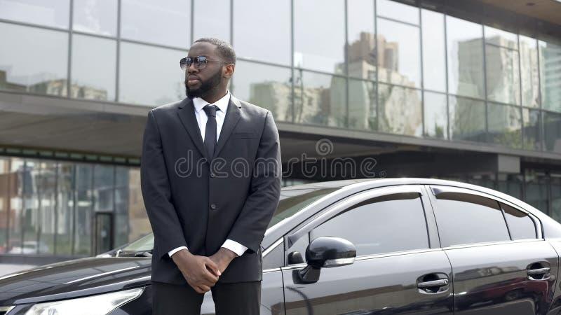 Jefe de seguridad afroamericano enorme de la orden de la supervisión fuera del centro de negocios imagen de archivo