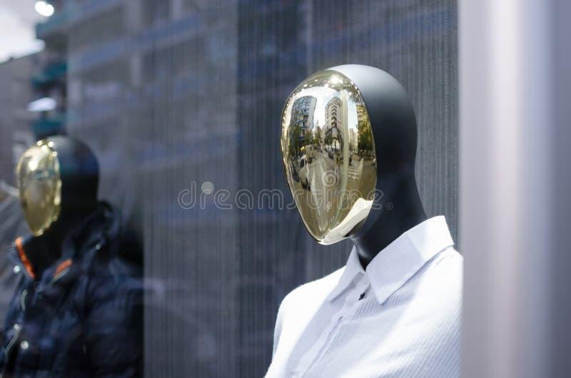 Jefe de un maniquí con una capa del oro en la ventana de la tienda imagen de archivo