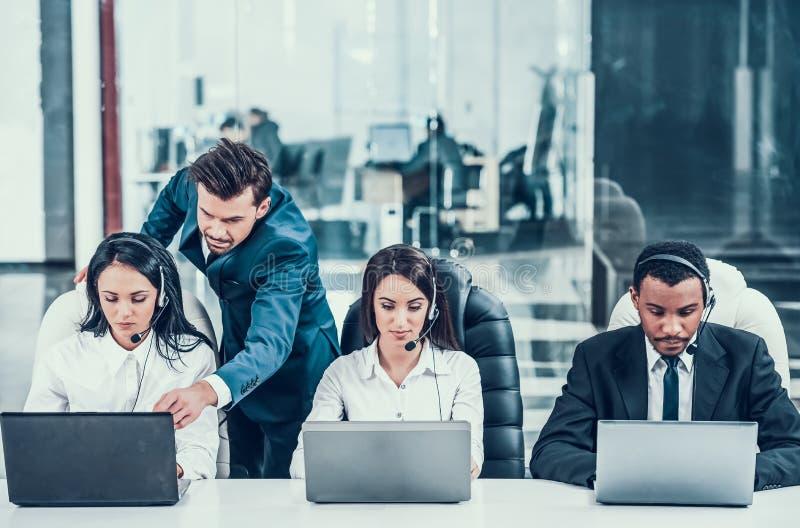 Jefe en centro de atención telefónica detrás de empleados multirraciales imagen de archivo libre de regalías