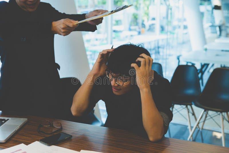 Jefe enojado que golpea al empleado con el documento en oficina foto de archivo