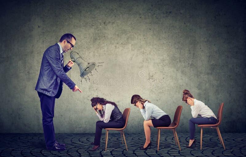 Jefe enojado que grita en el megáfono que da órdenes a la mirada triste abajo de empleados de sexo femenino fotografía de archivo libre de regalías