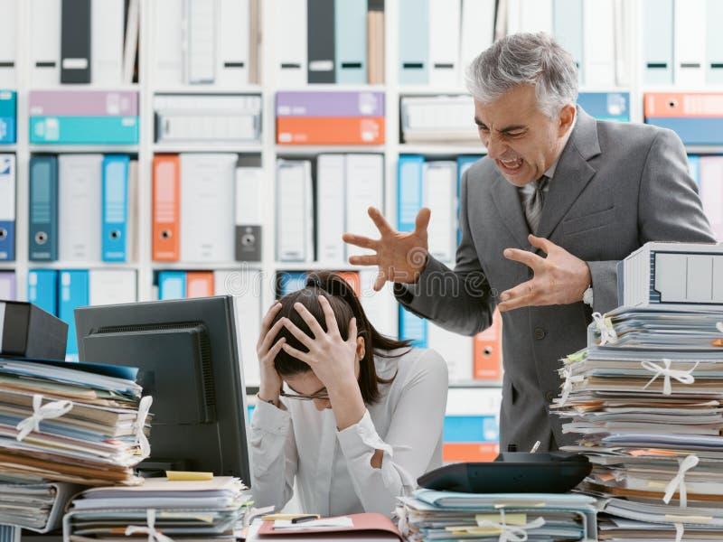 Jefe enojado que grita en su empleado joven imagen de archivo