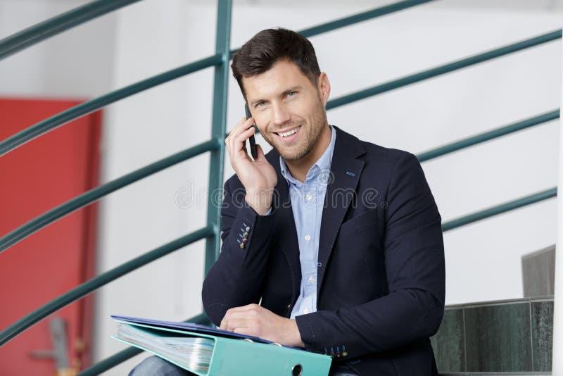 Jefe hermoso que invita al teléfono en escalera fotografía de archivo libre de regalías