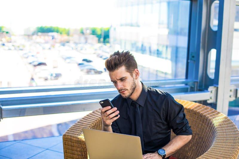 Jefe masculino pensativo usando los apps en el teléfono inteligente imagenes de archivo