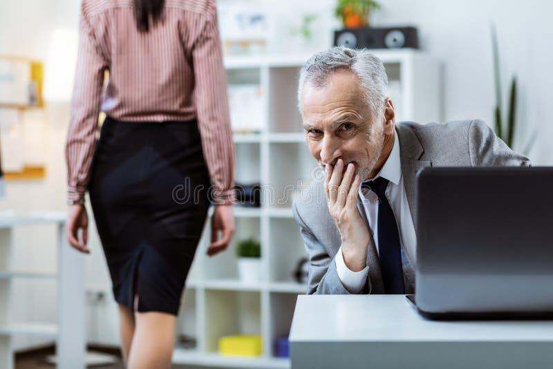 Jefe mayor gris-cabelludo sonriente que observa provocativo a su trabajador fotos de archivo libres de regalías