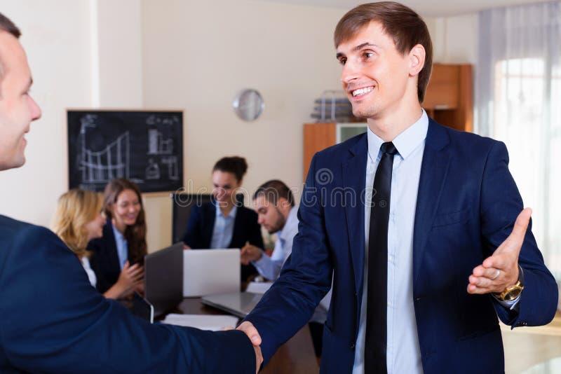 Jefe que saluda a un empleado y que sacude las manos fotos de archivo libres de regalías