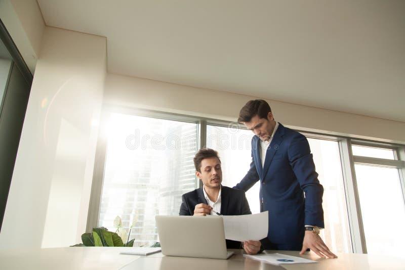 Jefe serio que habla con el empleado, divulgando sobre el proyecto, mostrando fotografía de archivo libre de regalías