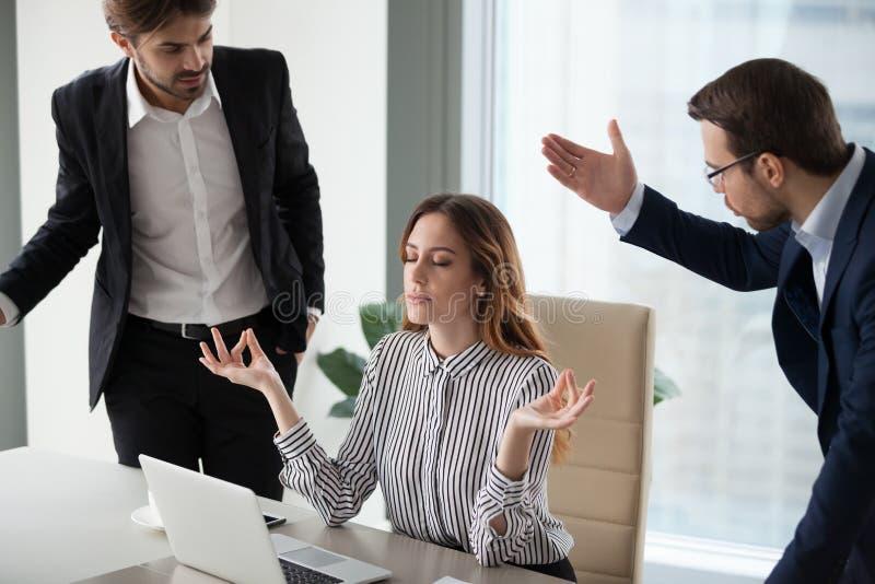 Jefe tranquilo atento de la mujer que medita en el trabajo que ignora a colegas enojados foto de archivo libre de regalías