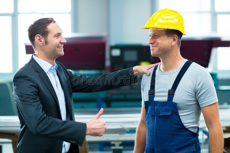 Jefe y trabajador jovenes en fábrica fotos de archivo