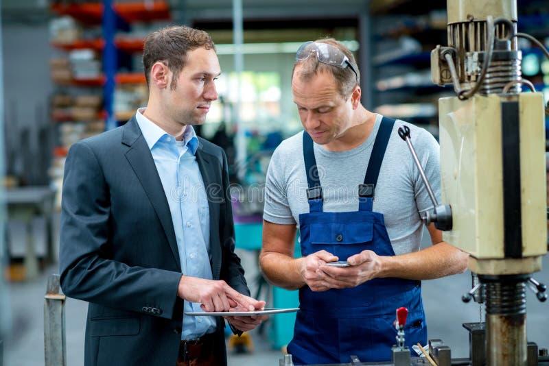 Jefe y trabajador jovenes en la conversación imagen de archivo libre de regalías