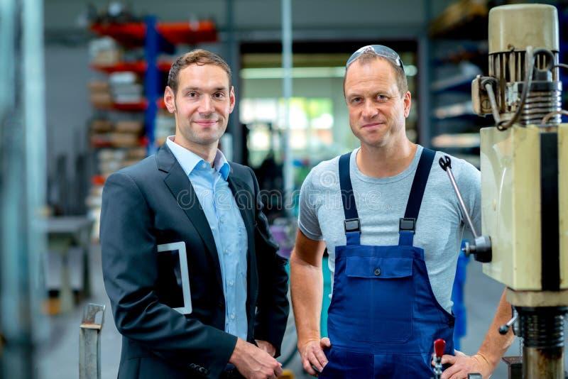 Jefe y trabajador jovenes en la fábrica fotos de archivo