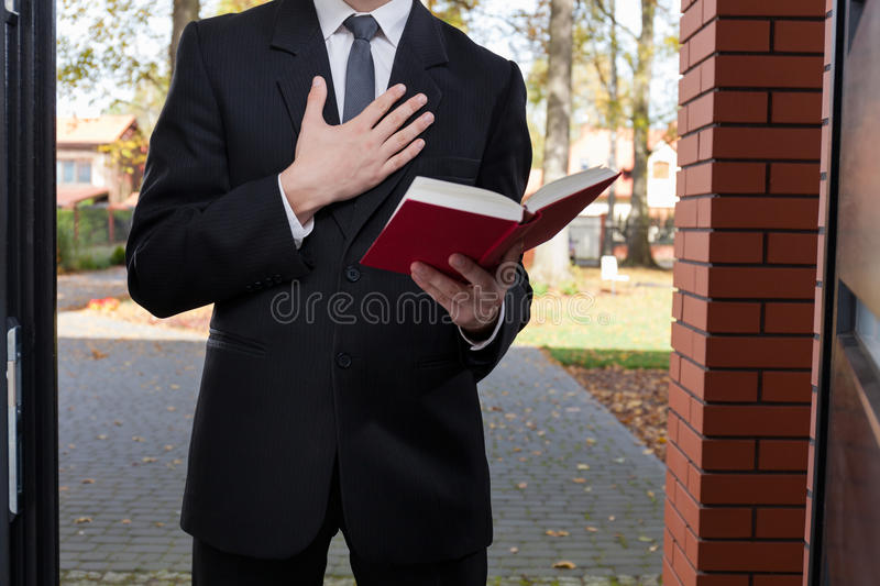 Jehovah's witness standing at the door. And holding Bible royalty free stock photos