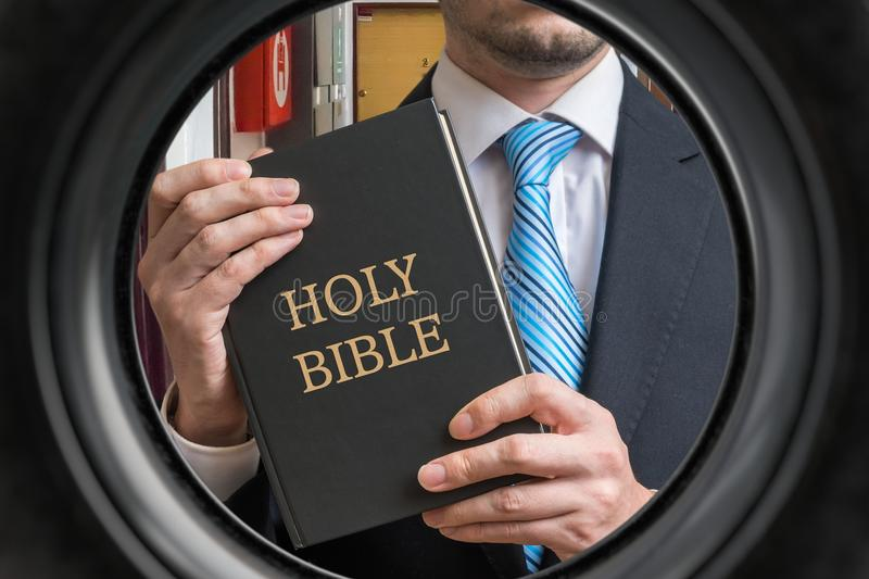 Jehovah witness is showing bible behind door. View from peephole.  royalty free stock photography