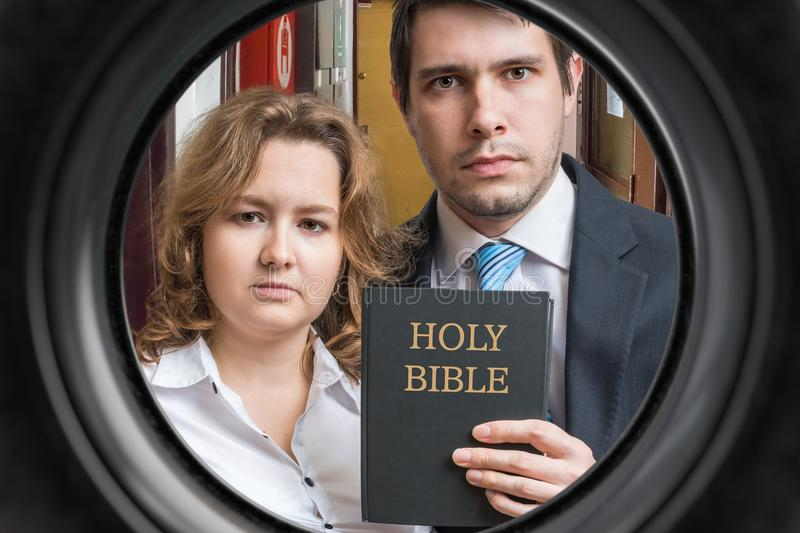 Jehovah witnesses are showing bible behind door. View from peephole.  stock image
