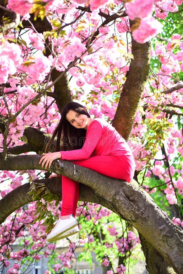 Jej przypadkowy styl Ładna dziewczyna z mody spojrzeniem Modna młoda dama na kwiatonośnym drzewie Mała dziewczynka w mody odzieży zdjęcie royalty free