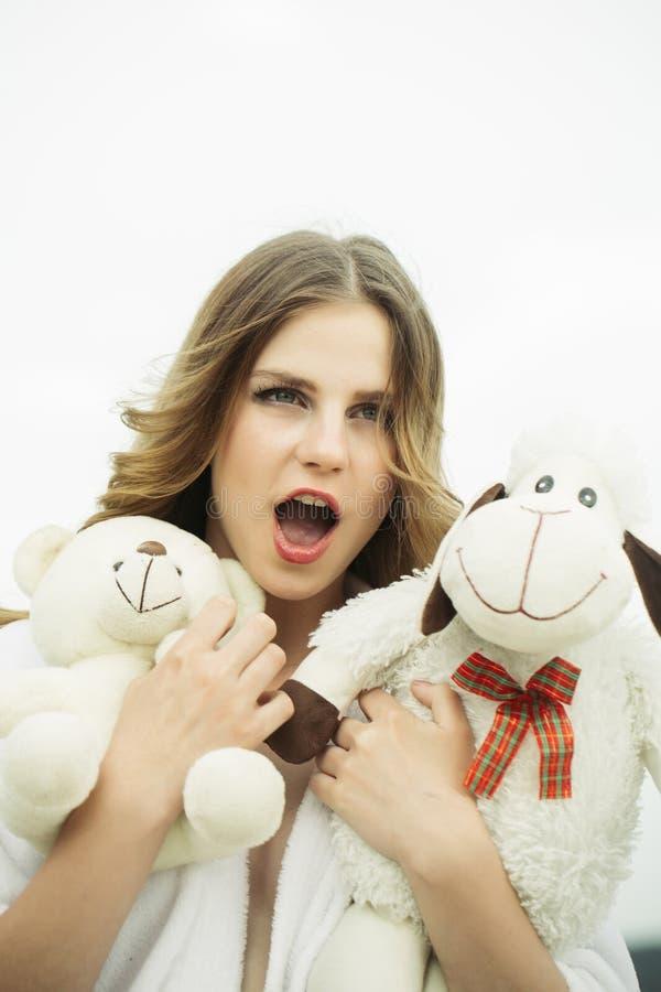 Jej pupil zabawki Kobieta z otwartymi usta chwyta zabawkami Młoda kobieta z miękkimi zwierzętami Piękno dziewczyna z makeup sztuk zdjęcia royalty free