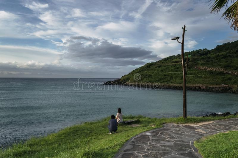 Man is taking picture of sitting woman on Jeju stock images