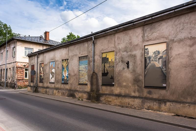 Old stone building with colourful paintings instead of windows stock photo