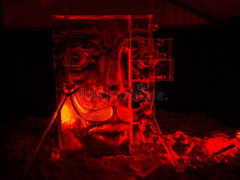 Jelgava / Latvia - February 10th, 2017: Big Carved face ice sculpture at night of International Ice Sculpture Festival in Jelgava. Red light royalty free stock images