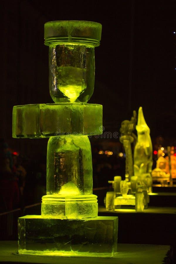 Jelgava/Letónia - 10 de fevereiro de 2017: Escultura de gelo amarela do relógio do tempo iluminado na noite do festival internaci fotos de stock