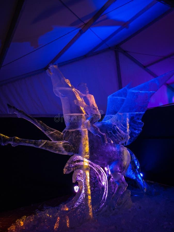 Jelgava/Letonia - 10 de febrero de 2017: Carvedboy en un caballo con la escultura de hielo de las alas en la noche de la escultur foto de archivo libre de regalías