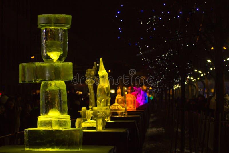 Jelgava/Lettland - 10. Februar 2017: Gelbe Uhr-Eisskulptur der beleuchteten Zeit, mit anderen Skulpturen im Hintergrund nachts vo stockfotografie