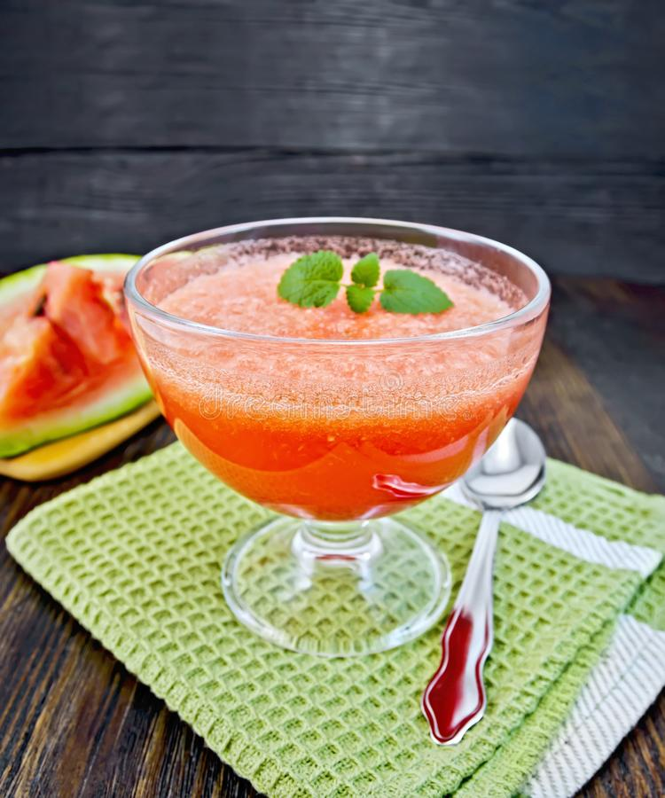 Jelly airy watermelon with mint on board. Jelly airy watermelon with mint in a glass bowl, spoon on a green towel on a background of a dark wooden board stock image
