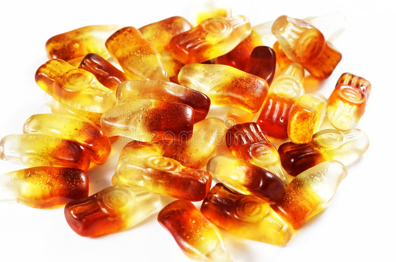 Jelly bean Cola flavored, isolated on white. Jelly bean Cola flavored gummy sweet in the shape of cola bottles, isolated on white stock images
